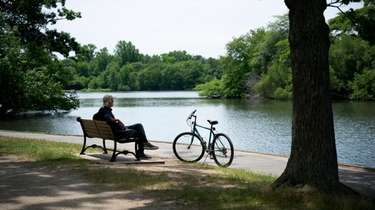 A bicyclist takes a break at Belmont Lake