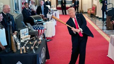 President Donald Trump tries out a baseball bat