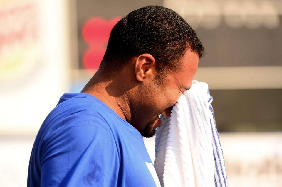 Johan Santana wipes his face after playing catch
