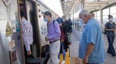 Commuters wearing masks board a train Thursday in