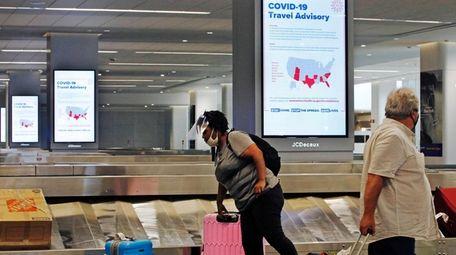 An arriving passenger wearing a face shield, left,