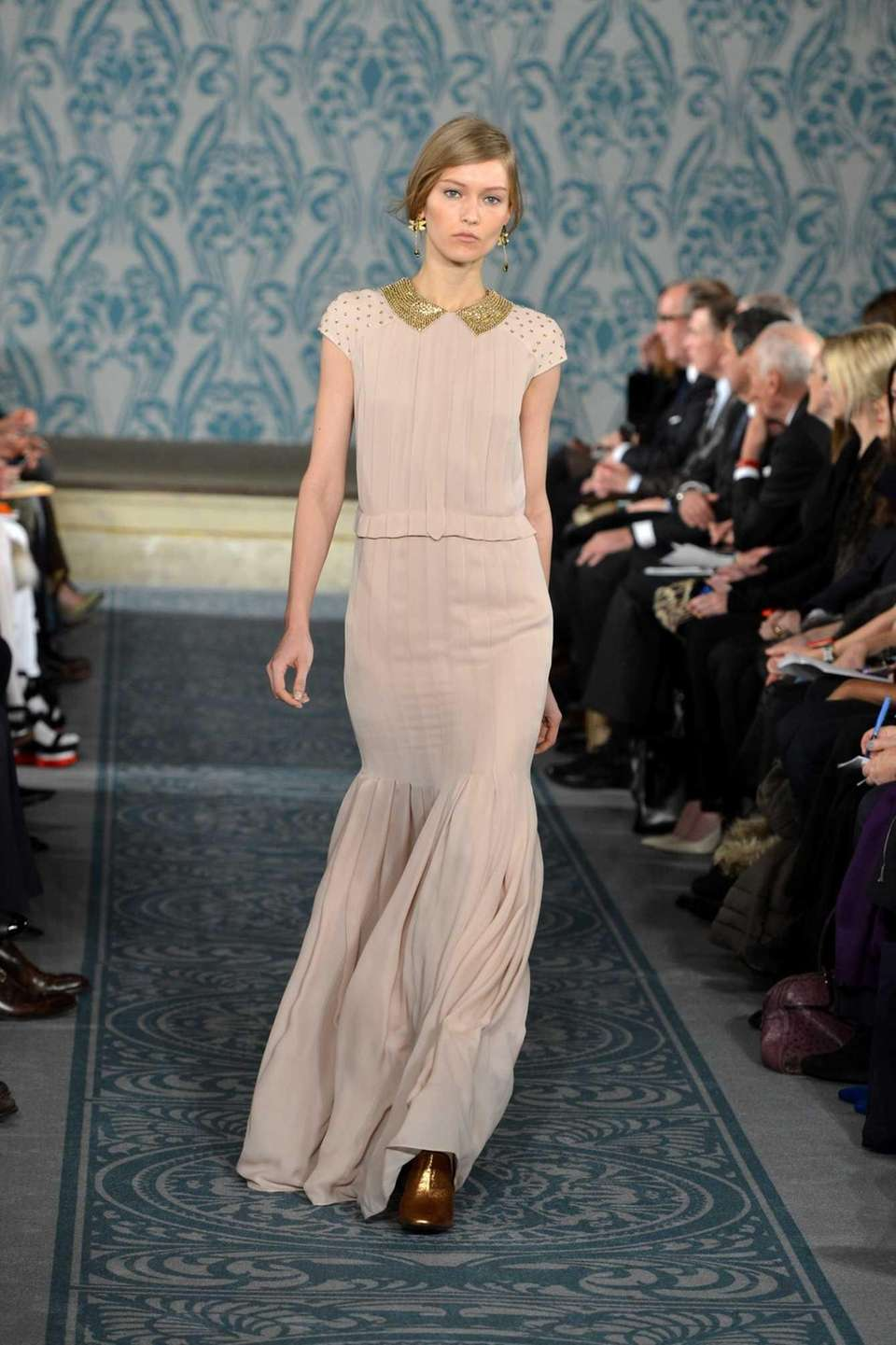 A golden, slim-fitting dress featured at the Tory
