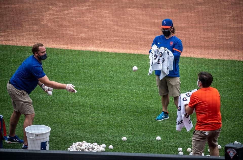 New York Mets team personnel clean baseballs after
