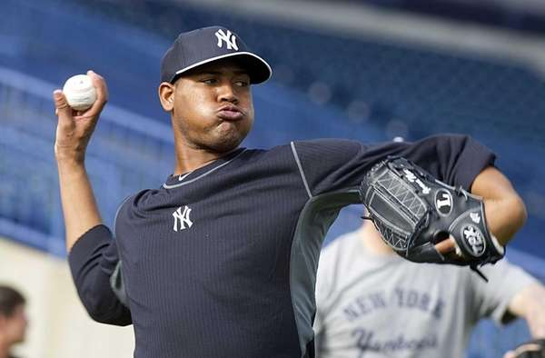 Yankees' Ivan Nova warms up his arm during