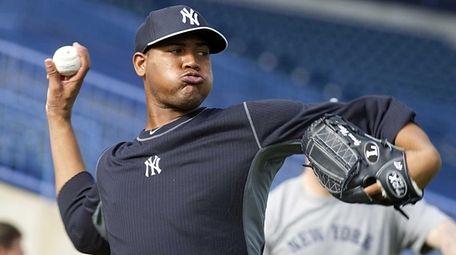 Yankees' Ivan Nova warms up his arm during