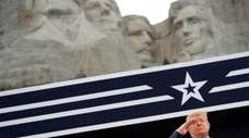 U.S. President Donald Trump salutes as he listens