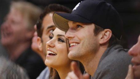 Actress Mila Kunis and actor Ashton Kutcher sit