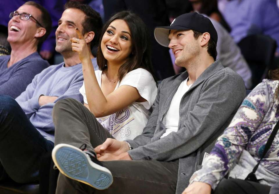 Actress Mila Kunis and Ashton Kutcher sit courtside