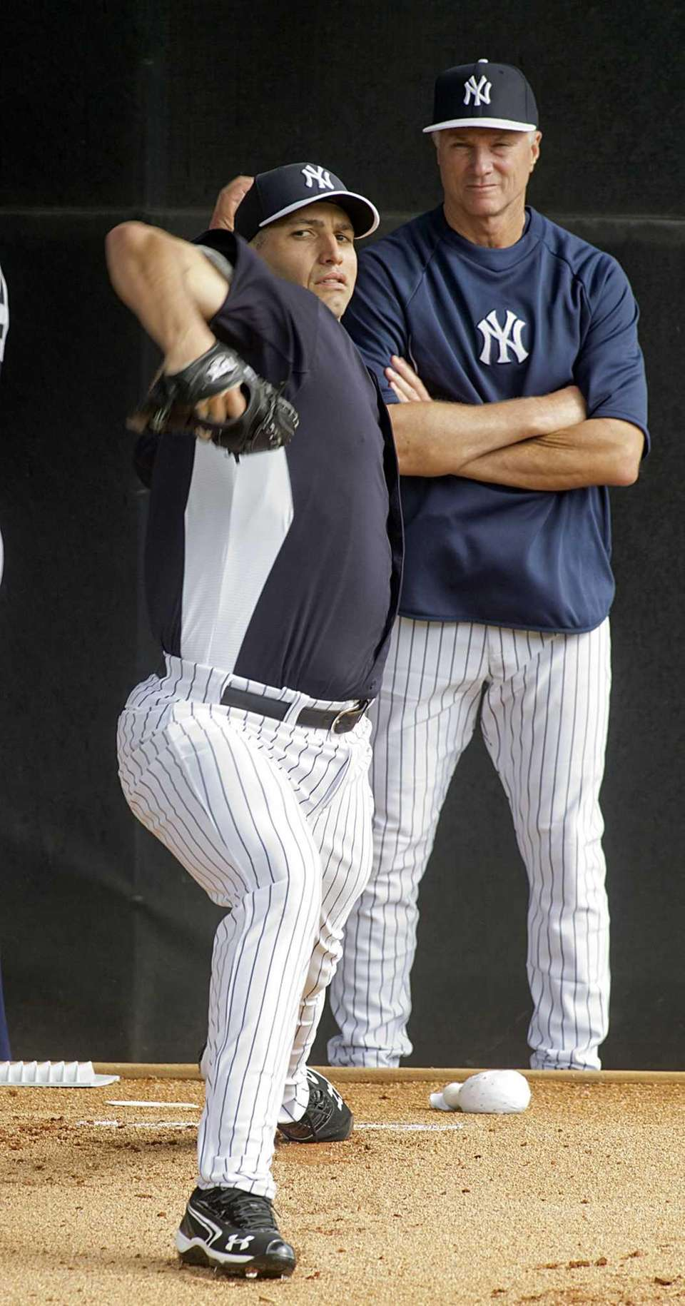 Andy Pettitte delivers a pitch as instructor Gil