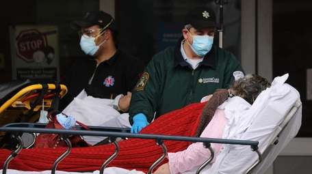 Medical workers transport a patient outside of a