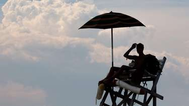 A lifeguard keeps watch over bathers as clouds