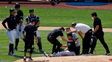 Yankees pitcher Masahiro Tanaka is tended to by