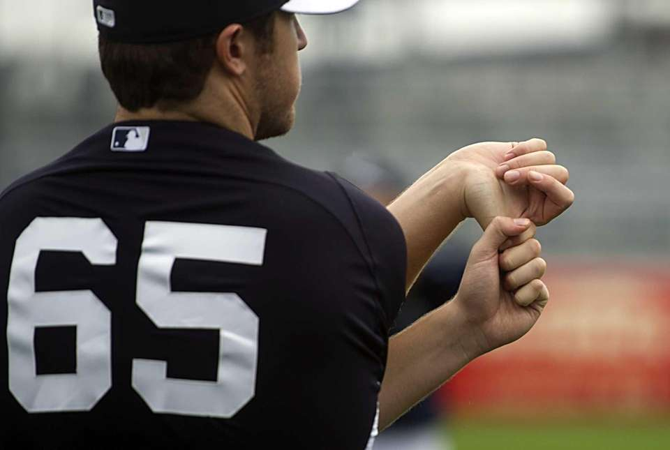 Phil Hughes stretches his arm before throwing at