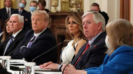 President Donald Trump, flanked first lady Melania Trump