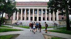 Students walk near the Widener Library at Harvard