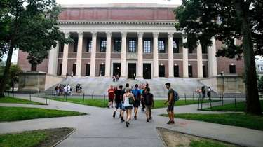 Students walk near the Widener Library at Harvard