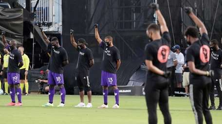 Orlando City players, left, raise their fists in