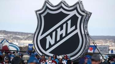 Fans pose below the NHL league logo at