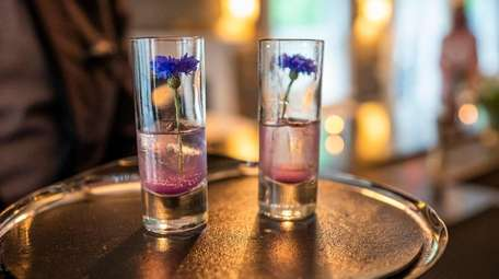 """A blue cocktail """"amuse"""" is made with cornflower-infused"""