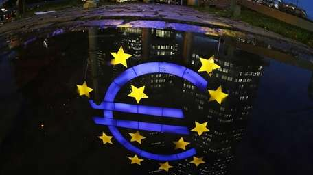 The giant Euro symbol is reflected outside the