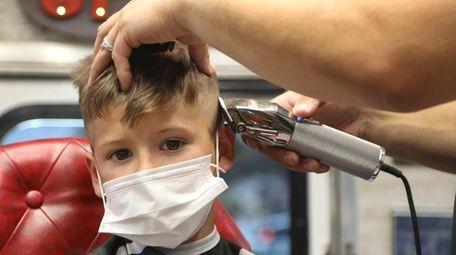 Jaxson Ronan, 6, gets his hair cut from