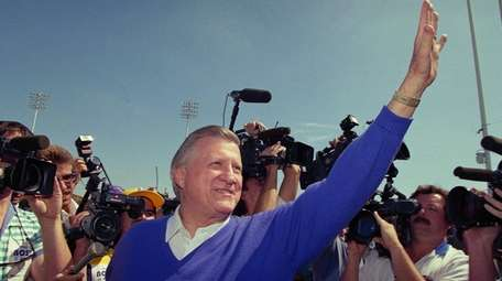 George Steinbrenner waves to a crowd of cheering