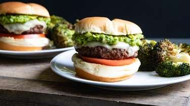 A burger topped with Cheddar cheese and guacamole.