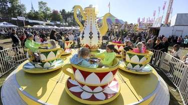 Children ride the tea cups during the Long