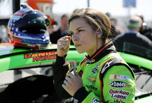 Danica Patrick removes her earplugs by her car
