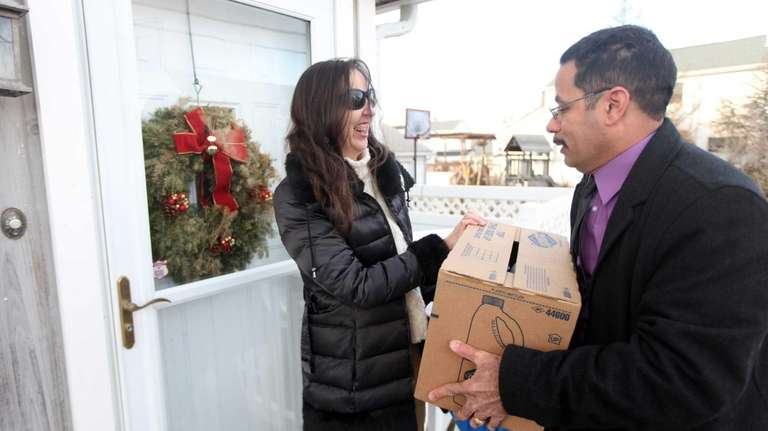 Luis Suarez, right, hands Mary Rogers disaster relief
