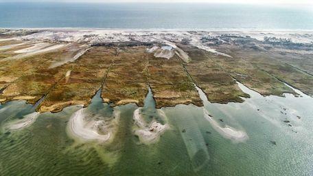 Sediment overwash flows into the salt marsh in