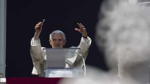 Pope Benedict XVI acknowledges a cheering crowd of