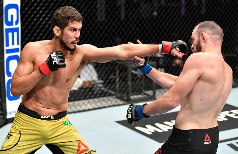 Leonardo Santos of Brazil punches Roman Bogatov of