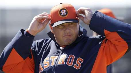 Houston Astros special instructor Roger Clemens adjusts the