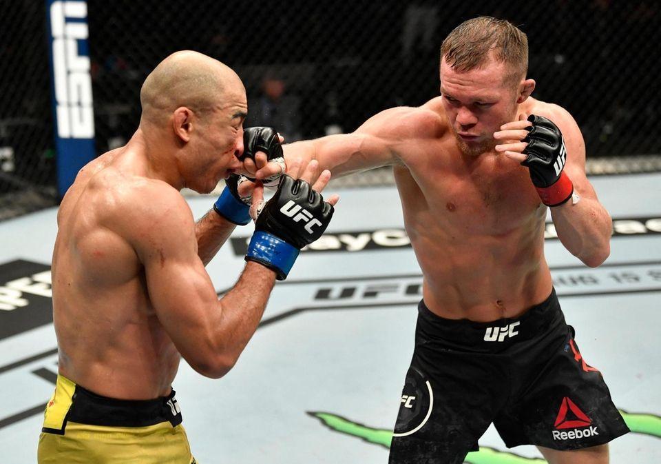 Petr Yan of Russia punches Jose Aldo of