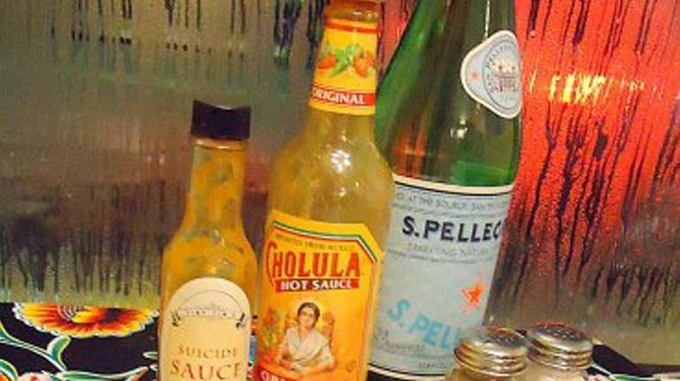 A menu and hot sauces on the