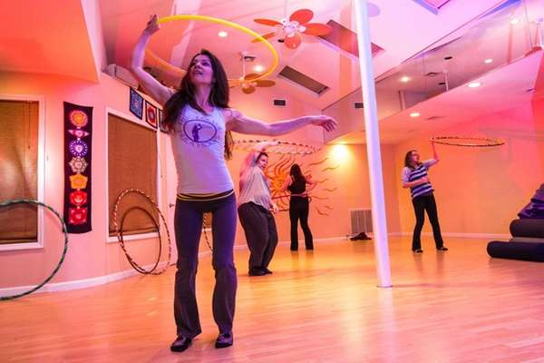 Instructor Jami Doria, of Huntington, leads a class in Hula-Hooping to music at Absolute Yoga Studios in Woodbury. In the back, from left are Kara Murphy and Meggan Murphy, both from Medford, and Joanne Valardi, of Centereach. (Feb. 13, 2013)