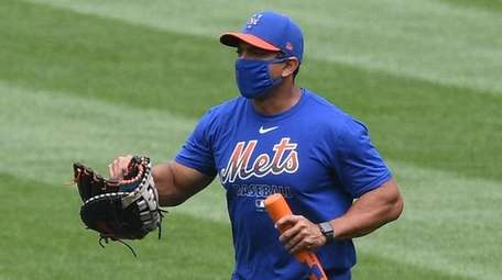 Mets manager Luis Rojas walks in the outfield