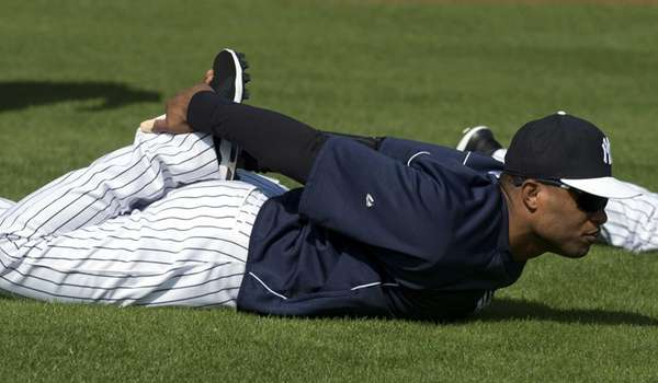 Yankees' Robinson Cano stretches while warming up for