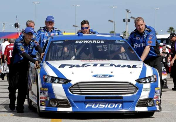 Crew members push the Fastenal Ford of Carl