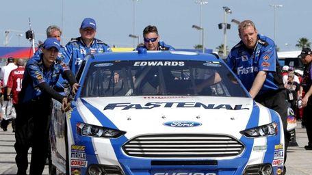 Crew members push the Fastenal Ford of Carl