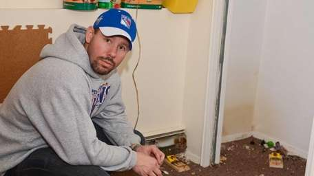 Chris Panza crouches inside his children's play room