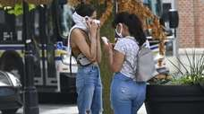 Two women wear protective face coverings while out