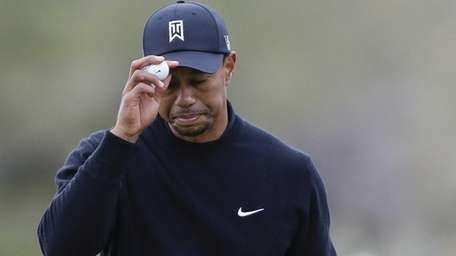 Tiger Woods tips his hat to fans after