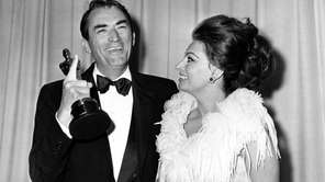 Gregory Peck indicates his one Oscar after winning