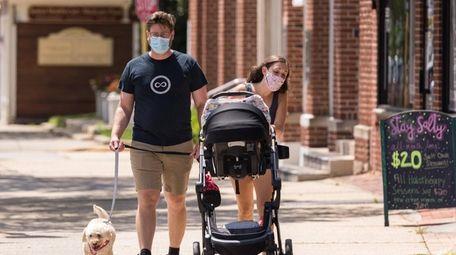 A masked couple, walking along Main Street in