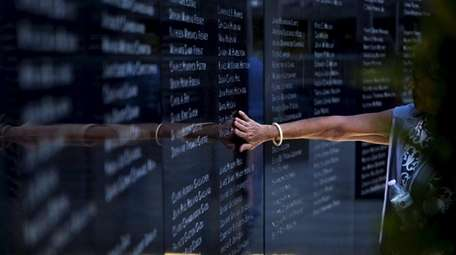 A mourner rubs her hand over the names
