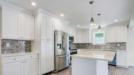 The custom kitchen has quartz countertops and stainless