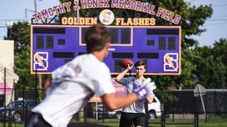 Sayville quarterback Jack Cheshire throws to a teammate