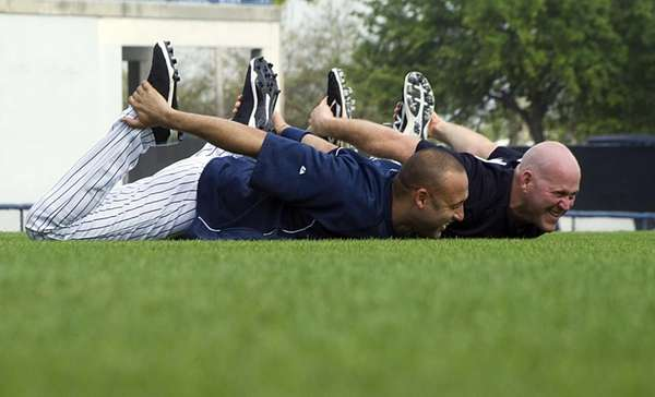 Derek Jeter and Kevin Youkilis stretch during warmups